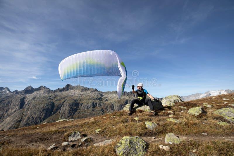 滑翔伞飞行员坐岩石并且在湖Grimsel附近平衡他的在他的头上的滑翔伞在瑞士阿尔卑斯山脉 免版税库存照片