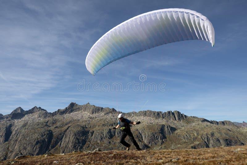 滑翔伞飞行员离开以他的滑翔伞离开和飞行入谷在瑞士阿尔卑斯山脉 库存照片