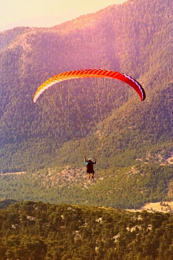 滑翔伞飞行在高地的 滑翔伞在黎明 拍从高度的照片 免版税图库摄影