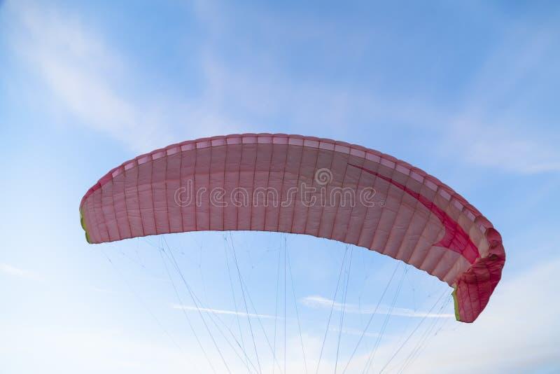 滑翔伞飞行桃红色圆顶在蓝色明亮的天空的 库存图片