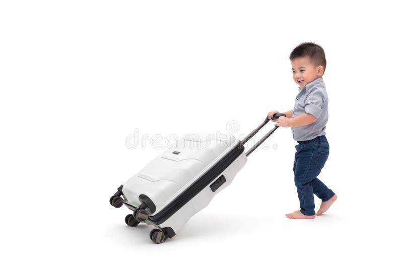 滑行李旅行包的愉快的亚裔男婴 免版税库存照片