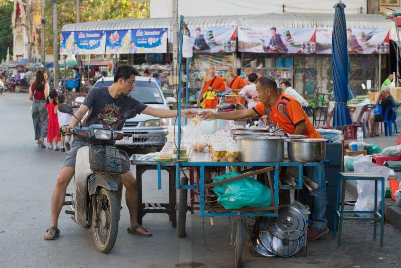 滑行车的年轻泰国人支付食物在摊贩 免版税库存图片