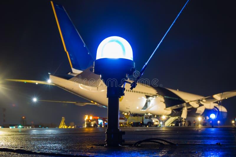 滑行道,在一台大客机的背景的旁边行光在夜机场围裙的 免版税库存照片