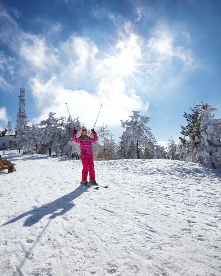 滑雪下坡在晴朗的冬日的愉快的小女孩 免版税图库摄影