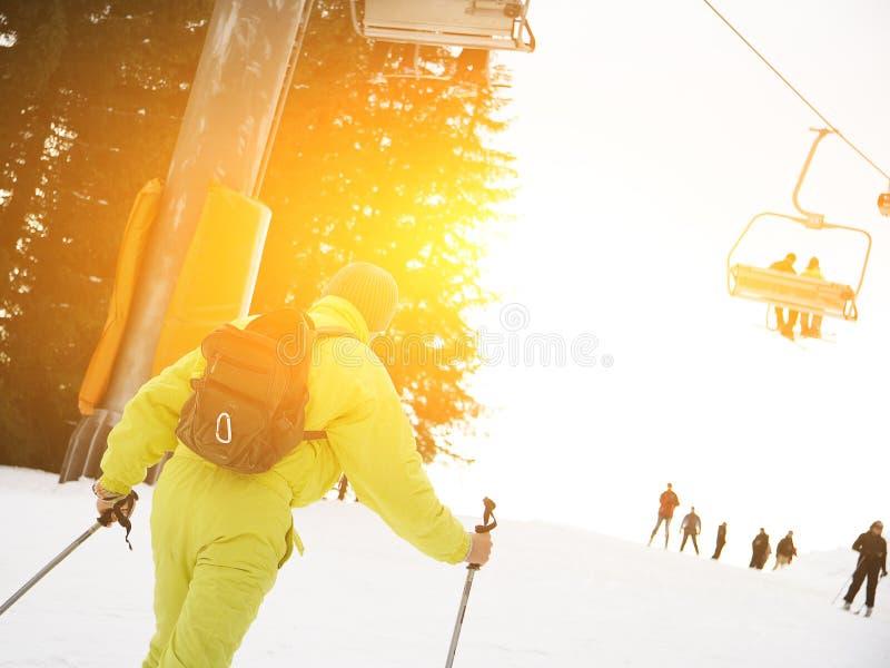 滑雪下坡在滑雪胜地的男性滑雪者反对滑雪吊车 图库摄影