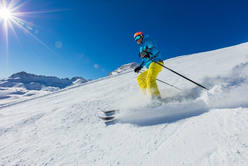 滑雪下坡在阿尔卑斯的年轻人 免版税库存照片
