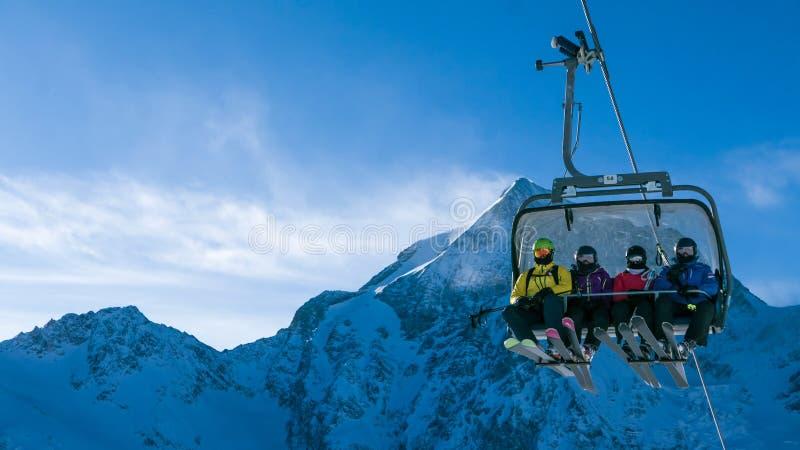 滑雪假日-滑雪者家庭驾空滑车的 库存照片