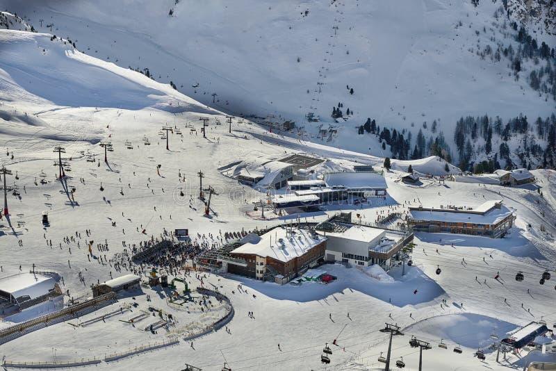 滑雪基地在蒂罗尔阿尔卑斯在晴朗的12月天 驾空滑车和缆车到处都是人,人群是在入口前面 咖啡馆a 库存照片