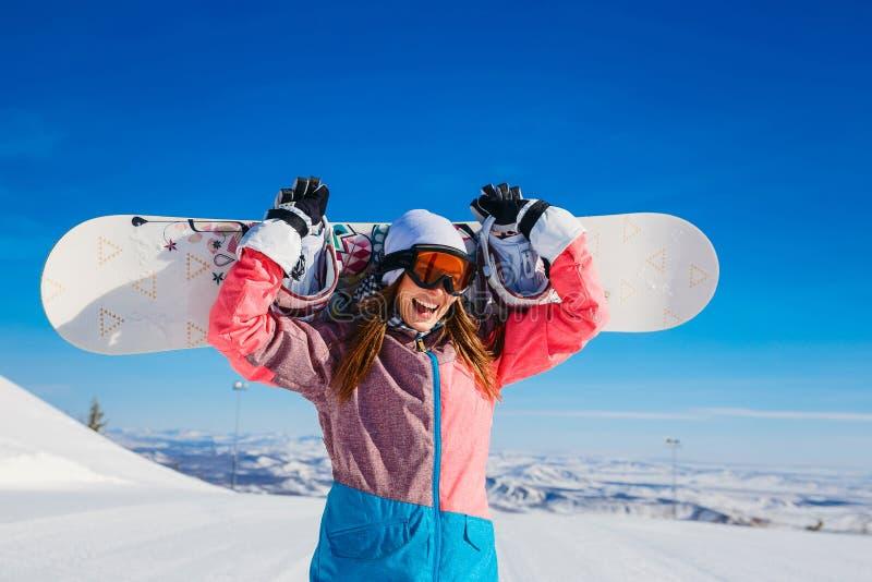 滑雪服和玻璃的愉快的快乐的妇女在冬天在她的手上拿着一个雪板 极其 库存图片