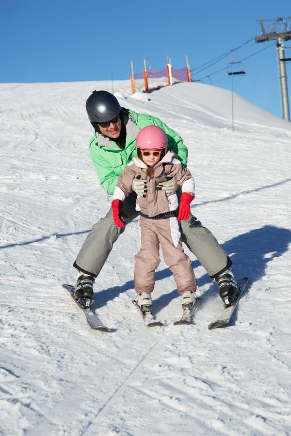 滑雪的父亲教的女儿,在度假 库存图片