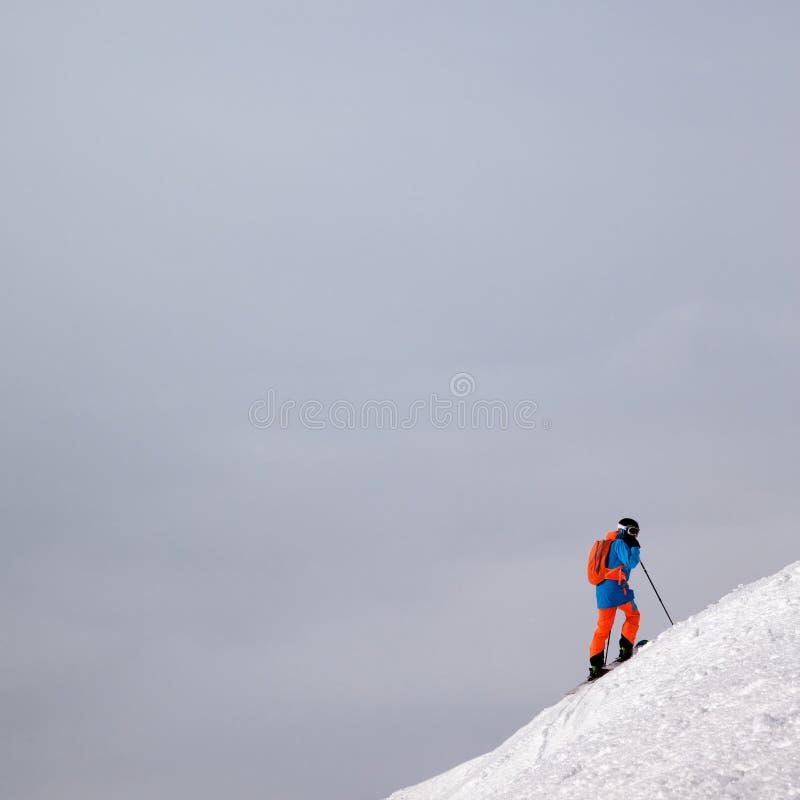 滑雪者前面下坡freeriding和阴云密布的多雪的倾斜的 免版税库存图片
