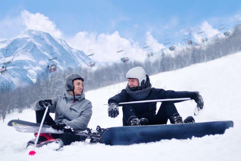 滑雪者和挡雪板在滑雪和雪板运动休息以后,坐谈话,笑以山为背景 滑雪和snowboar 免版税库存图片