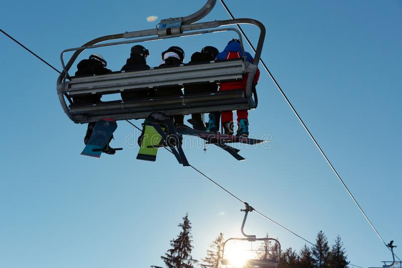 滑雪者和挡雪板滑雪电缆车的反对天空蔚蓝在山在寒假 库存图片