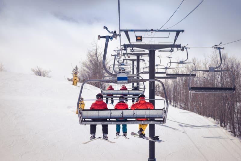 滑雪者和挡雪板驾空滑车的 免版税库存图片