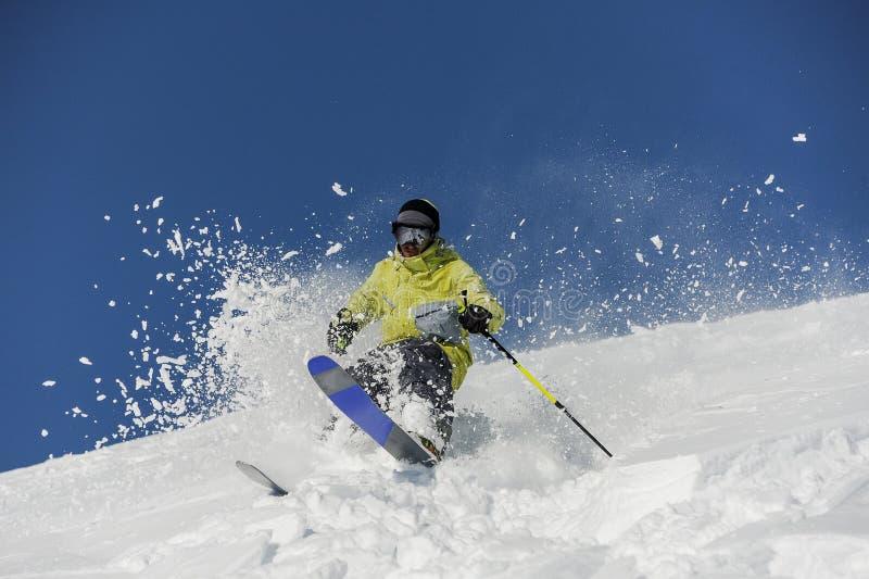 滑雪者在乘坐在倾斜下的黄色运动服穿戴了在Geor 库存图片