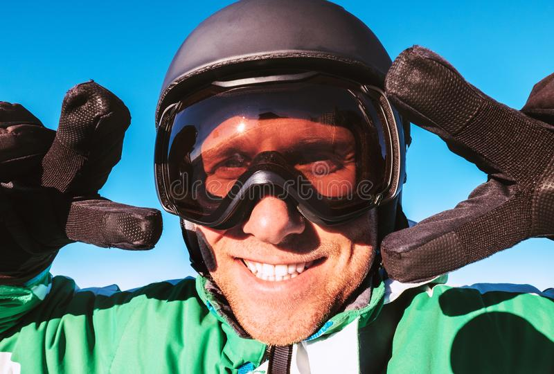 滑雪者在显示两个`胜利`姿态画象的滑雪盔甲和滑雪风镜穿戴了 免版税图库摄影