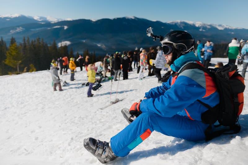 滑雪运动员坐雪反对山和人背景  免版税库存图片