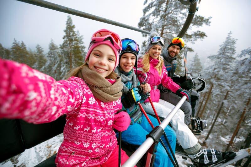滑雪,滑雪电缆车,滑雪胜地-滑雪电缆车的m愉快的家庭滑雪者 免版税库存图片