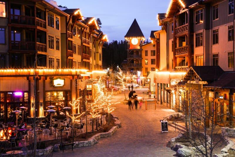 滑雪/雪板镇在晚上点燃了,与家庭乐趣在`村庄`马默斯Mountain,加利福尼亚美国 免版税图库摄影