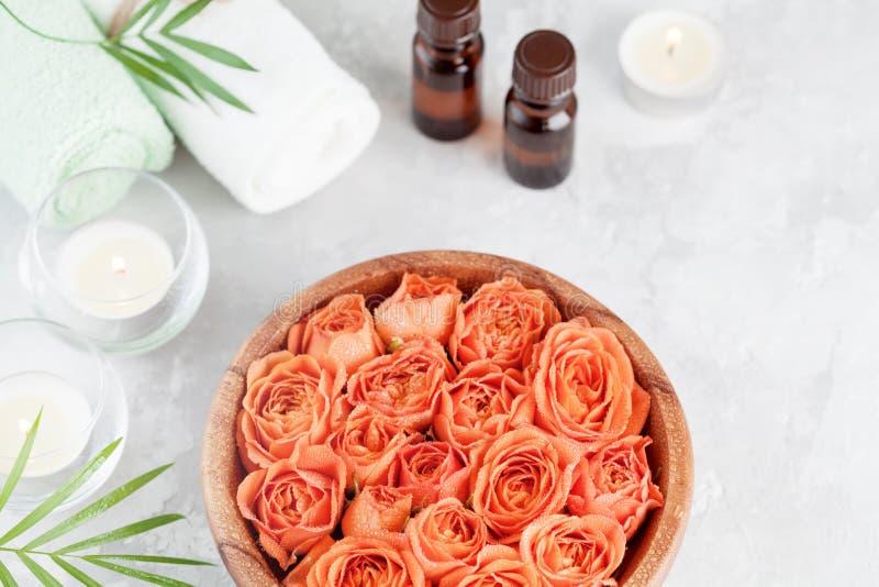 滚保龄球与新鲜弄湿温泉、健康和芳香疗法的玫瑰色和精油瓶 免版税库存图片