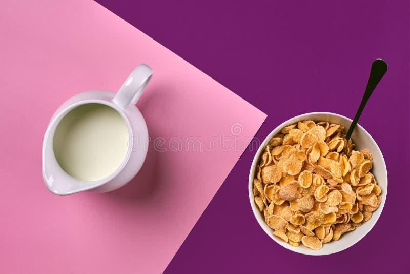 滚保龄球与玉米片、在紫色和桃红色背景,顶视图的水罐牛奶和匙子 库存图片