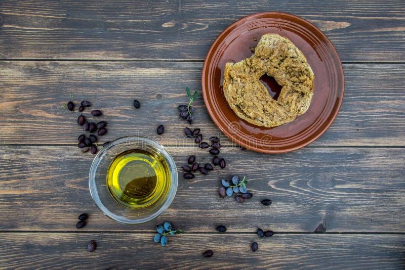 滚保龄球与额外处女橄榄油,橄榄,橄榄树一个新分支,并且克里特岛人面包干dakos在木桌,克利特, Gree上关闭  免版税图库摄影