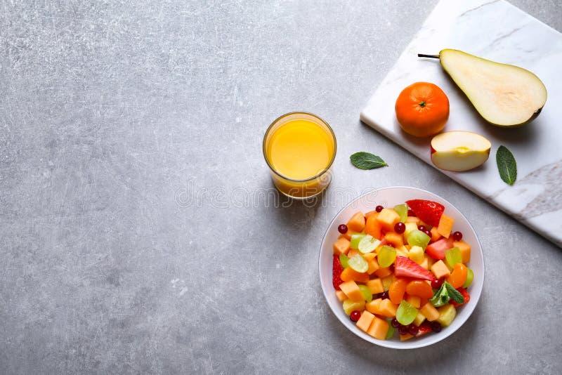 滚保龄球用新鲜水果沙拉和杯汁液 免版税库存图片