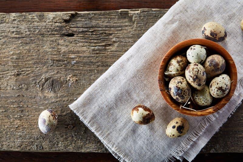 滚保龄球用鸡蛋鹌鹑,在一块手织的餐巾的鸡蛋在木背景,特写镜头,选择聚焦 免版税库存图片