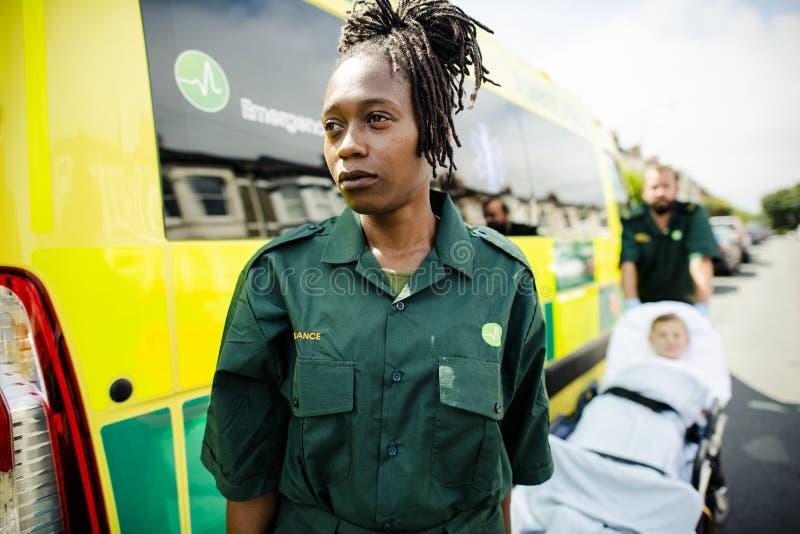 滚动一名年轻患者的医务人员在救护车担架 免版税库存照片