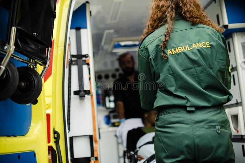 滚动一名年轻患者的医务人员在救护车担架 库存照片