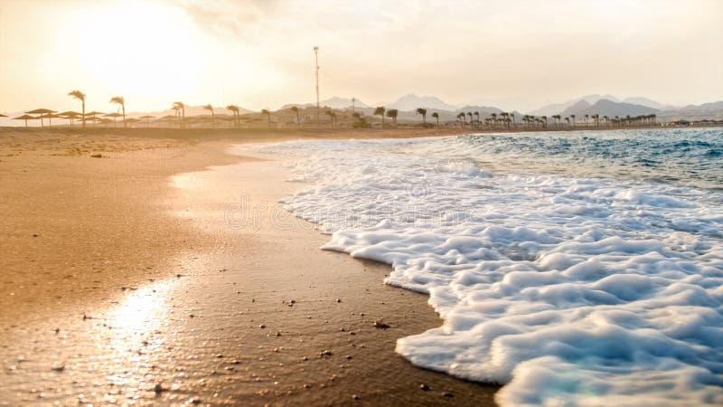 滚动在含沙海海滩的美丽的蓝色海浪特写镜头照片反对令人惊讶的日落 图库摄影