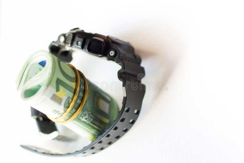滚动在被隔绝的现代手表里面锁着的传送带的一百欧元笔记在白色背景 黑手表与 库存图片