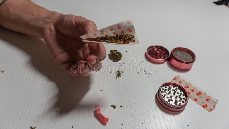 滚动的医疗大麻联接whith彩纸供以人员手 研磨机和大麻在白色桌上 免版税库存图片