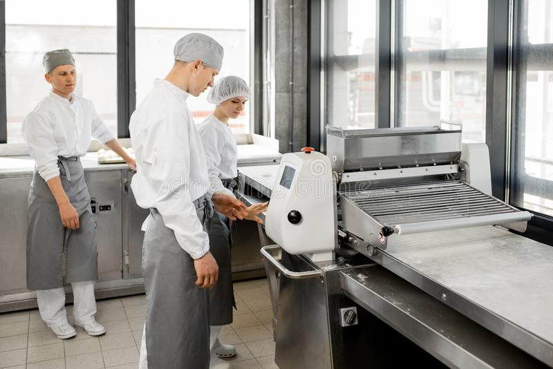 滚动面团的面包师在制造业 库存照片
