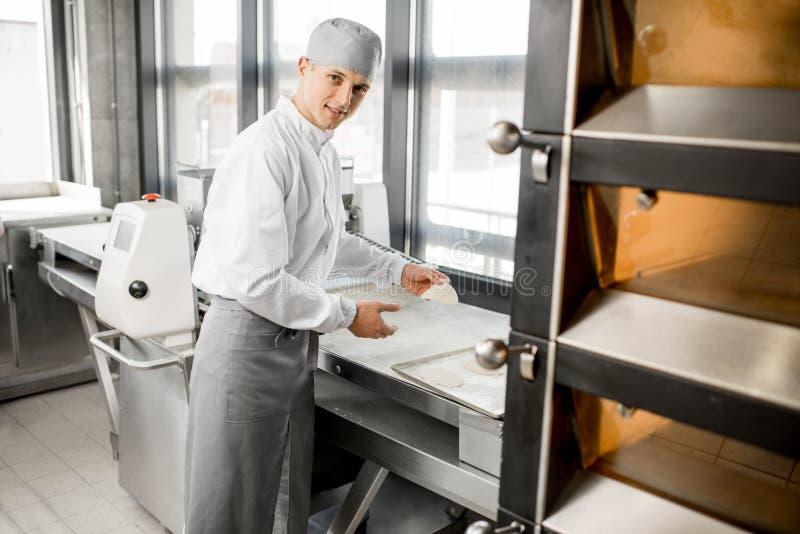 滚动面团的面包师在制造业 图库摄影