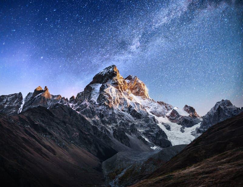 满天星斗美妙的天空 秋天风景和积雪覆盖的峰顶 主要白种人土坎 从登上Ushba迈尔的山景城 免版税图库摄影