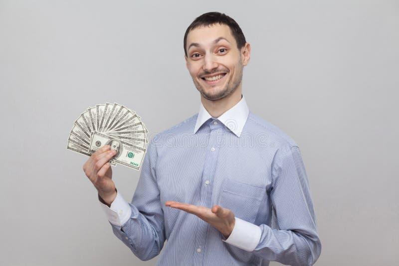 满意的可爱的年轻成人商人画象在站立,给和指向与金钱手指爱好者的蓝色衬衣的  免版税库存照片