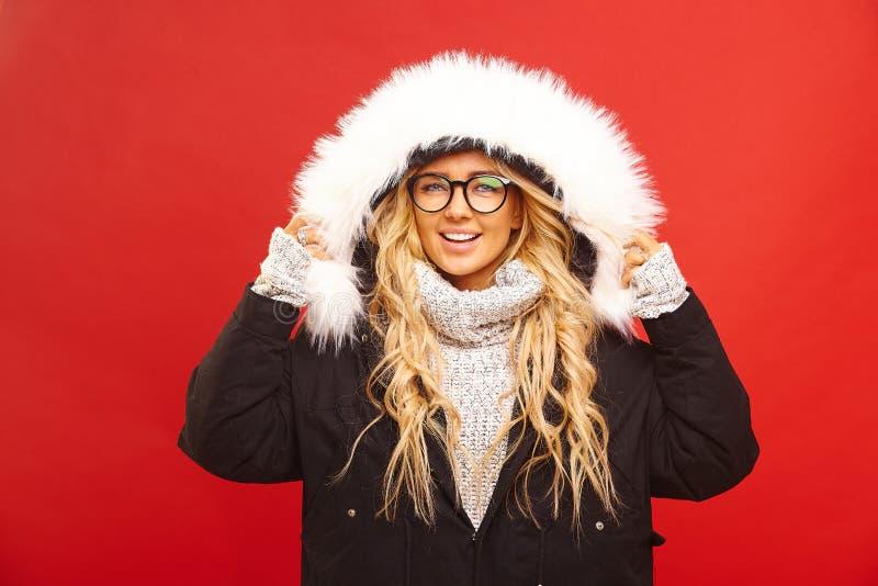 满意的妇女画象,穿有敞篷的一件温暖的冬天夹克,有快乐的表示,感到温暖和舒适 图库摄影