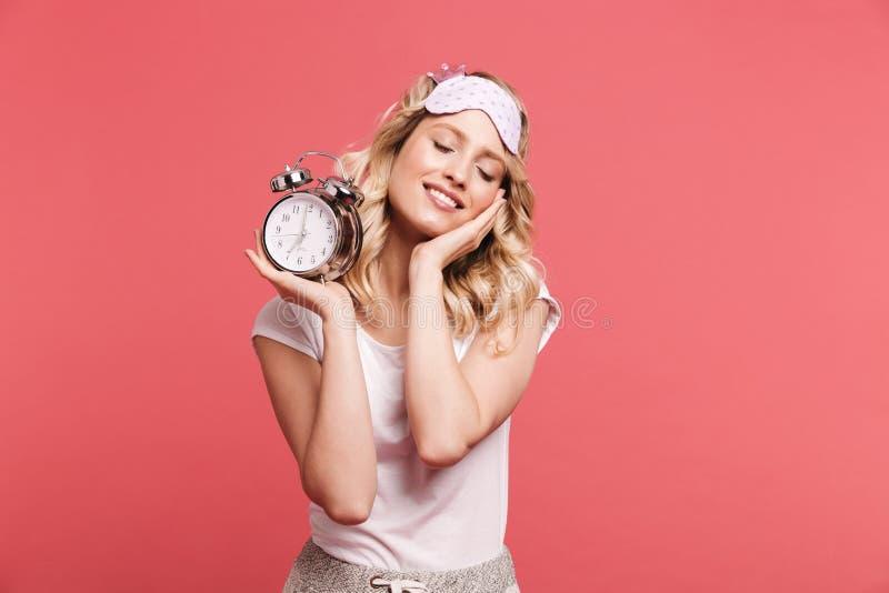 满意的年轻女人20s佩带的睡觉面具藏品闹钟画象在唤醒以后的 库存照片