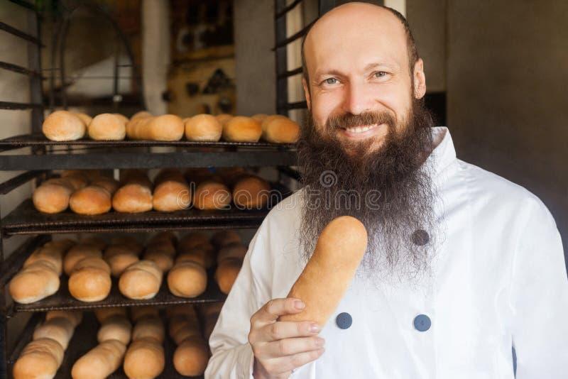 满意的年轻成人厨师画象有长的胡子的在白色一致的身分在他的面包店和拿着新鲜面包,看 库存照片