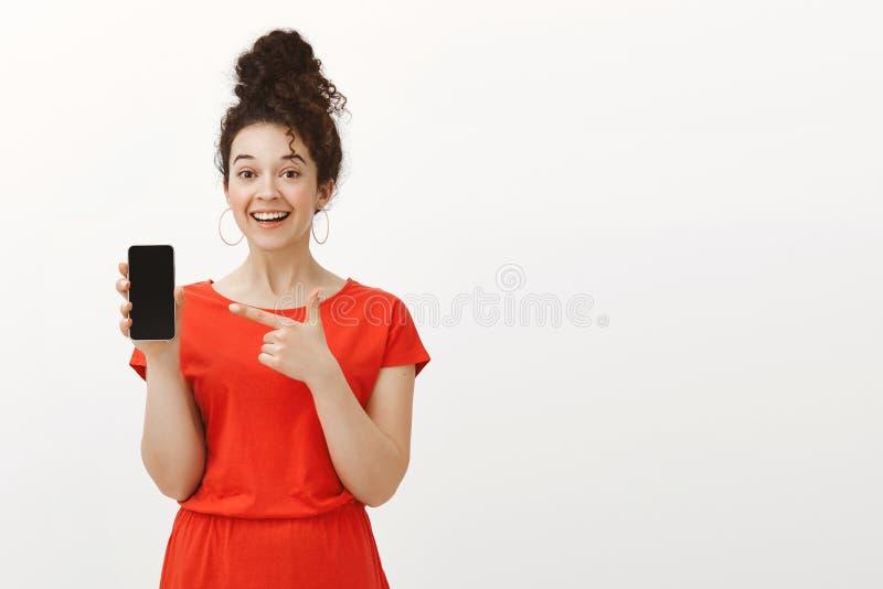满意的悦目女性画象红色礼服的有在小圆面包梳的卷发的,显示智能手机和指向在 库存照片
