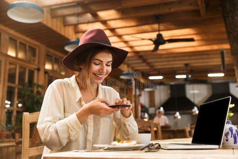 满意的拍摄在手机的妇女佩带的帽子画象食物 库存照片