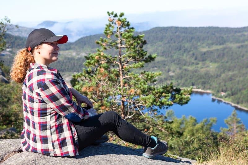 满意的欧洲妇女远足者享受山湖看法从高峭壁, copyspace的 库存图片