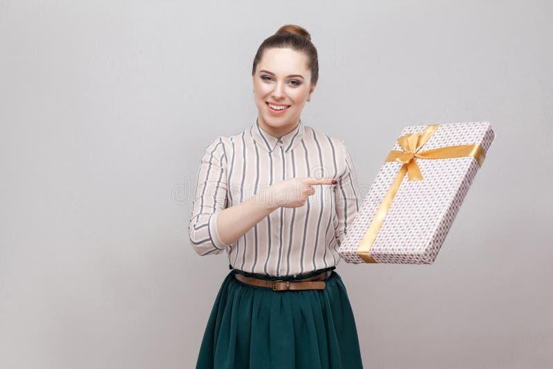 满意的美丽的年轻妇女画象站立和指向手指的便装样式的提出与黄色弓和 库存照片