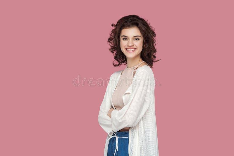 满意的美丽的深色的年轻女人画象有卷曲发型的在站立和看照相机与的便装样式 免版税库存图片