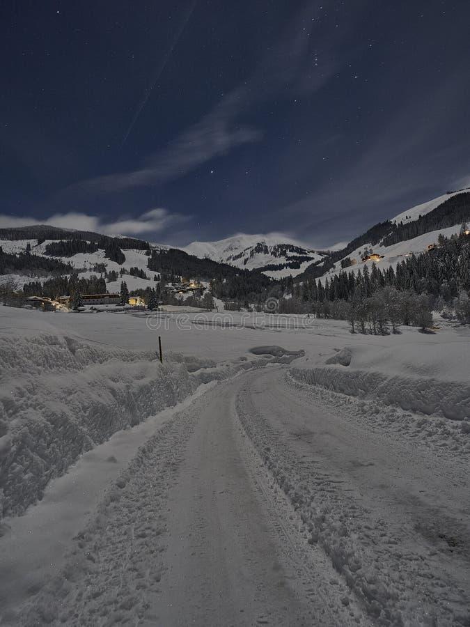 满月冬天夜童话,一条积雪的路 免版税库存图片
