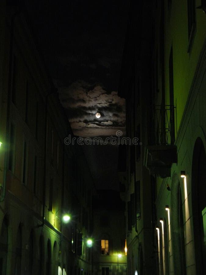 满月游泳通过在天空的云彩,打开他们 在一条街道上在科莫湖,意大利 免版税库存照片