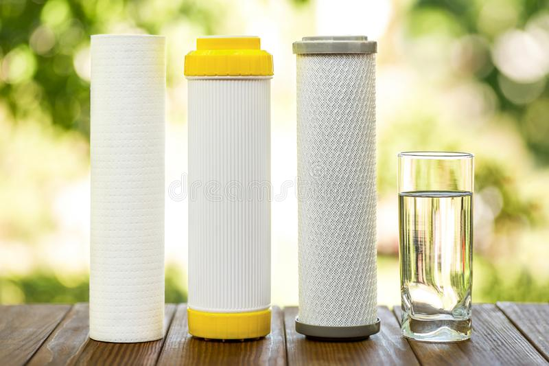 滤水器 碳弹药筒和一杯在木桌上的水在自然背景 家庭滤清系统 免版税库存照片