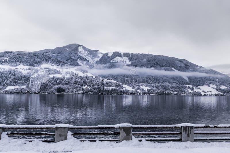 滨湖采尔萨尔茨堡-有大多雪的山的奥地利冷和冻湖在背景和雾覆盖上面 免版税库存照片