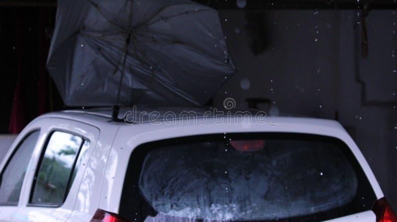 滴下从有汽车&伞的屋顶的雨在棚子下 库存照片